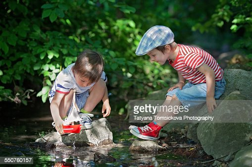 Lillle Boy Toys Boats : Cute little boys playing on a pond with toy boat stock