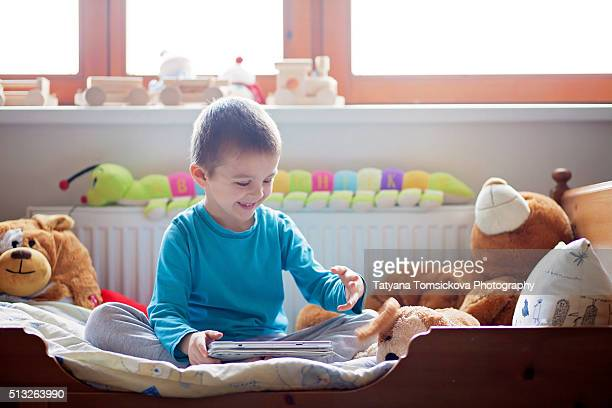 Cute little boy,sitting in bed in kids room, playing on tablet happily, stuffed toys around him