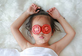 Cute little Child girl with a slice of tomato in her eye, concept for skin care.