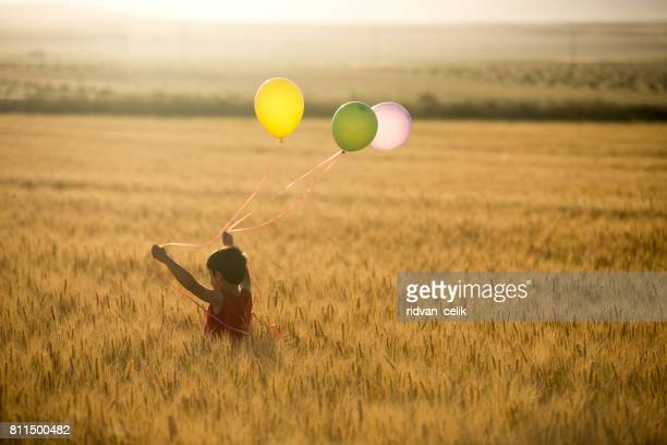 Cute little child with balloons at field