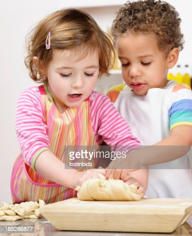 Cute Little Girl And Boy Kneading Dough