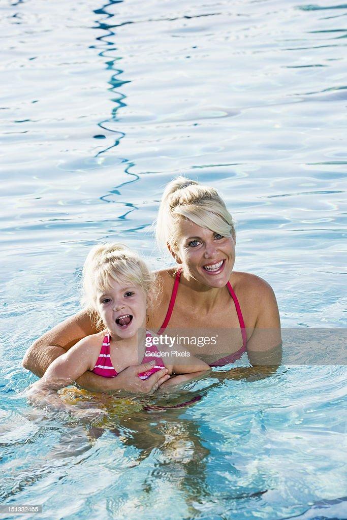 Cute little girl and mom having fun in pool : Stock Photo