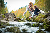 Sweet, cute little girl and mommy sitting on a rock in forest at stream. Enjoying fresh autumn air. Yellow trees. Karelia. Waterfall Kivach.