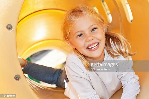 Cute Little Girl at top of playground slide tube
