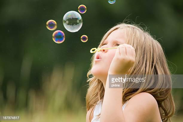 かわいい小さな女の子の吹く泡屋外
