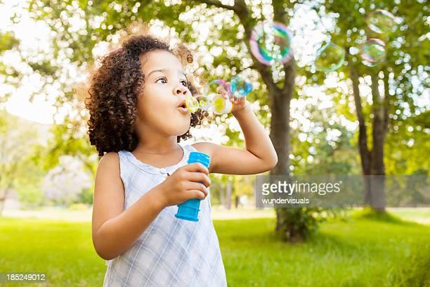 Mignonne petite fille souffle des bulles