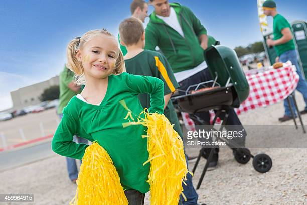 Cute little girl cheering for football team at tailgating party