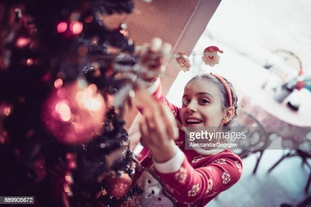 Niedliche kleine Mädchen schmücken ihre Tanne mit Christbaumschmuck