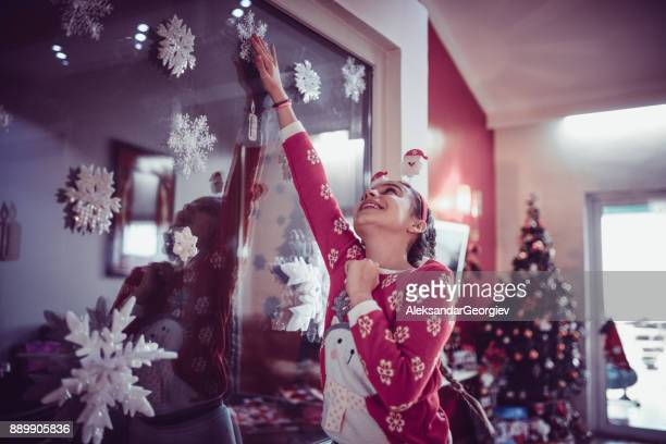 Niedliche kleine Mädchen schmücken ihr Zimmer mit Christbaumschmuck