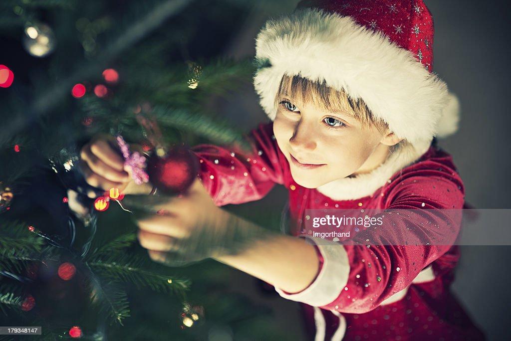 Cute little girl decorating christmas tree : Stock Photo