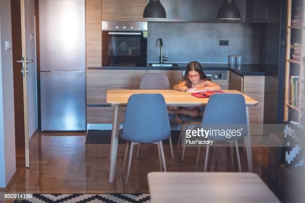 Niedliche kleine Mädchen, die Hausaufgaben in der Küche