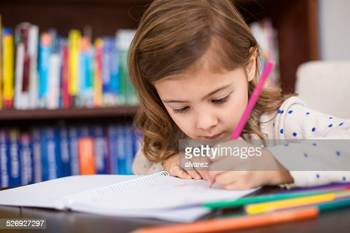 Cute little girl drawing with color pencils