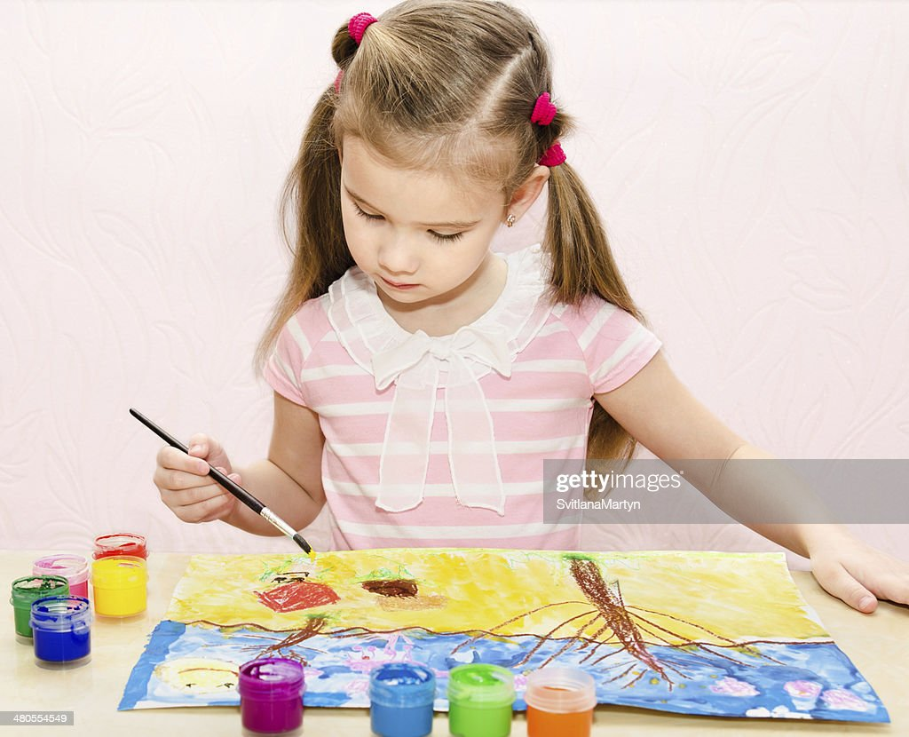 Cute little girl drawing with paint and paintbrush : Stock Photo