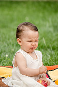 Cute little girl eating a sour apple