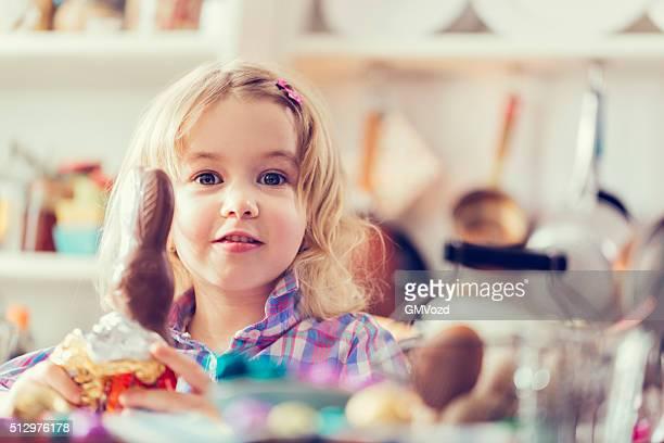 Lindo niña pequeña de comer el Chocolate conejo de pascua