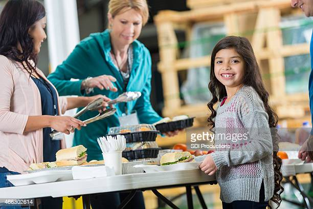 Cute little girl eating meal in community food bank kitchen