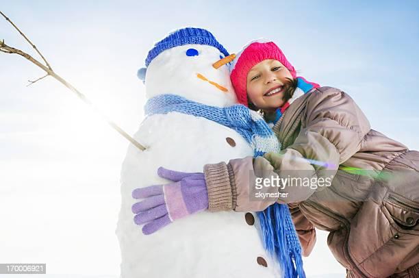 Cute little girl embracing her snowman.