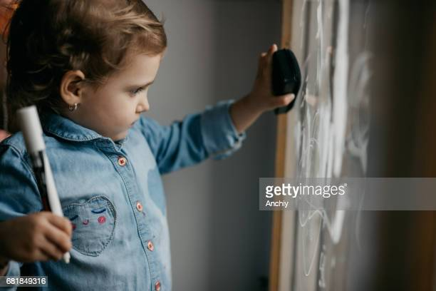 Cute little girl erases what is drawn on the window