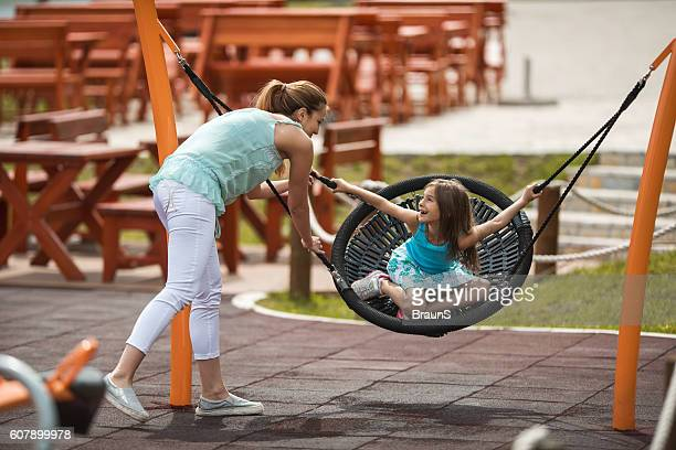 Cute little girl having fun with her mother on playground.