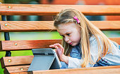 Cute little girl having fun with tablet in the park, playing video games. Lifestyle, technology concept