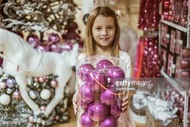 Cute little girl in christmas store holding big box with christmas balls