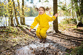 Cute little girl jumping in muddy puddle wearing yellow rubber overalls. Happy childhood. Sunny autumn forest