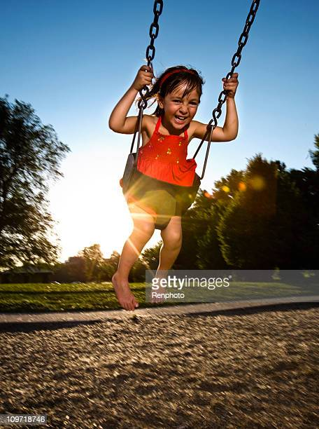 Cute Little Girl Laughing While Swinging at Playground