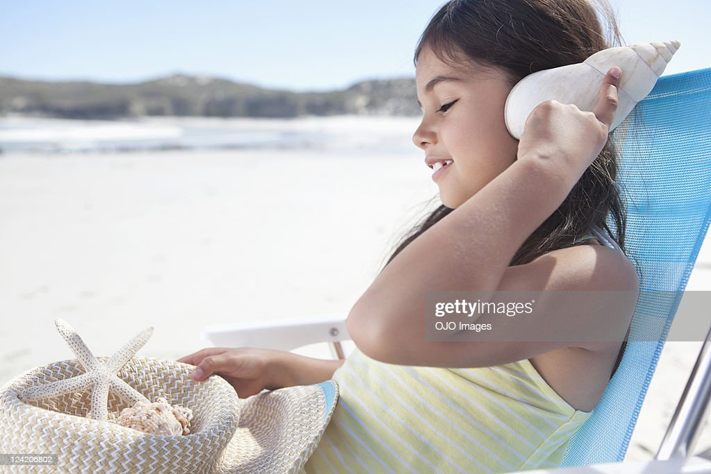 Cute little girl listening to sea shell with eyes closed at beach : Stock Photo