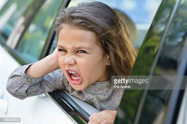 Cute little girl looking out of the car window