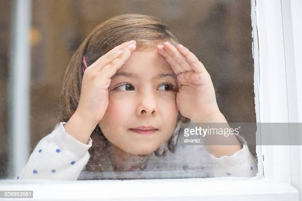 Cute little girl looking outside window