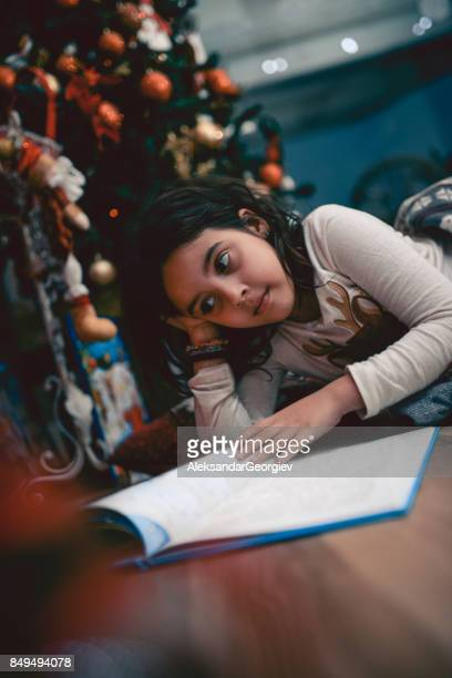 Cute Little Girl Lying Under Christmas Tree Wile and Reading Book