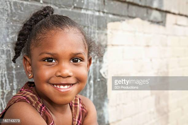Cute Little Girl next to wall with copy space