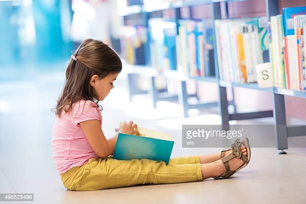 Rapariga engraçada no chão na biblioteca