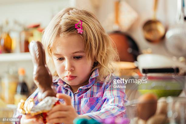 Cute Little Girl Opening Chocolate Easter Bunny