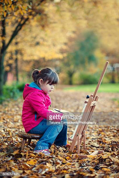 Cute little girl, painting in the park