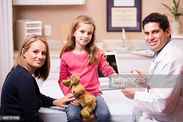 Niedliche kleine Mädchen Patienten mit einem Kinderarzt Arzt, Mutter. Lateinamerikanischer Herkunft.