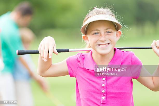 Cute little girl playing golf with father on green course