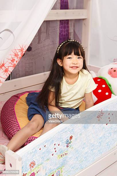 Cute little girl playing on the bed