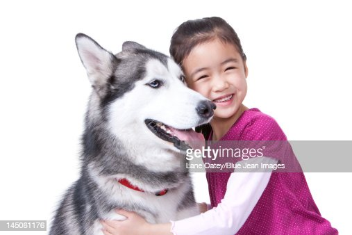 Cute little girl playing with a Husky dog