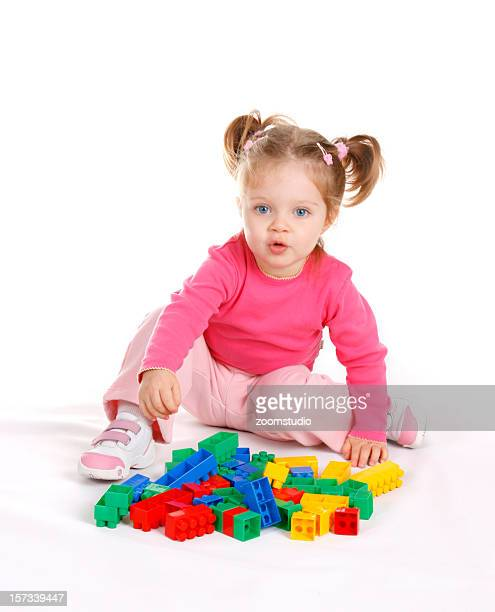 Cute little girl playing with blocks, on white background
