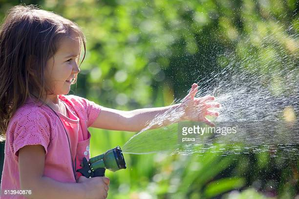 Cute little girl playing with water in the garden