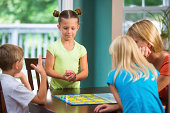 Authentic, fun image of a family playing a board game in a typical american home. Little girl with buns in hair shakes dice in her hands before her roll.