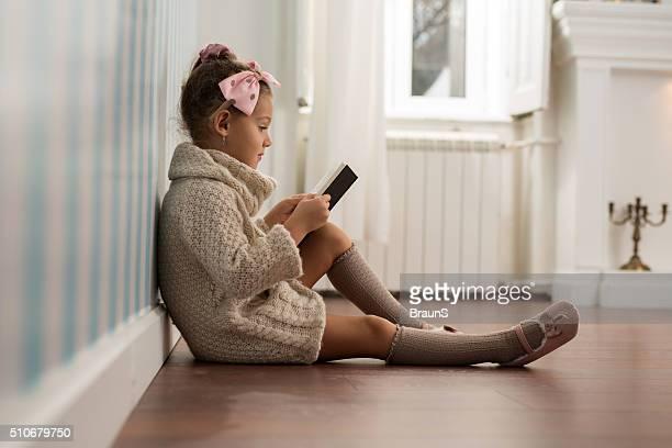 Joli fillette lisant un livre sur le sol.