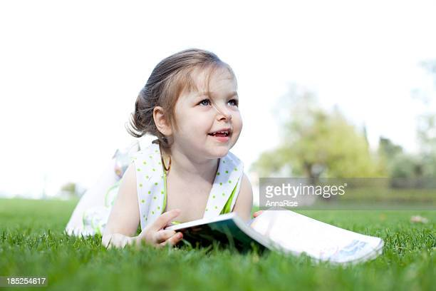 Cute Little Girl Reading Outdoors