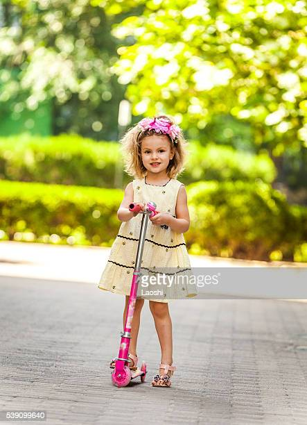 Cute little girl riding scooter