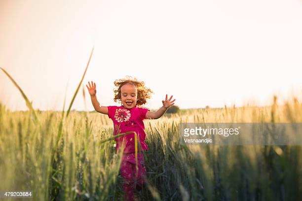 Rapariga engraçada a correr através do campo