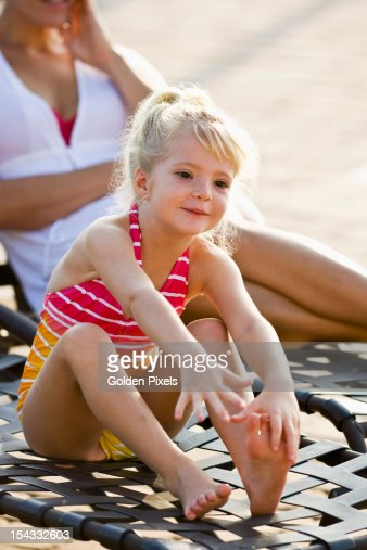 Cute little girl sitting in lounge chair : Stock Photo