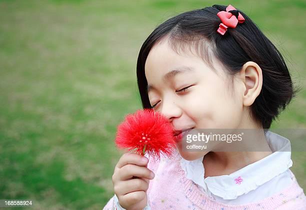 Süßes kleines Mädchen riechen Blumen