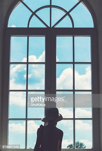 Cute little girl stands near a window : Stock Photo