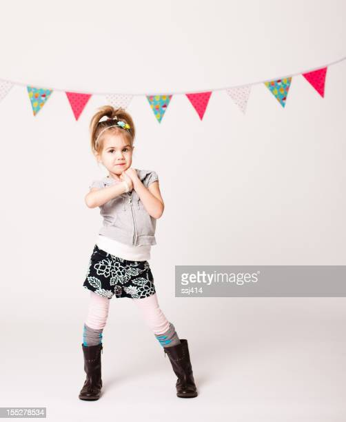 Cute Little Girl Strikes a Pose while on White Background